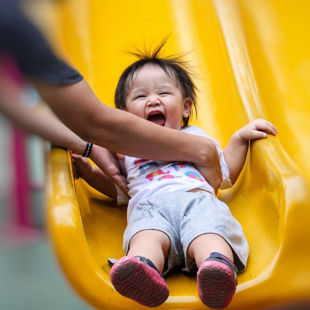 a small boy sliding down a playground slide