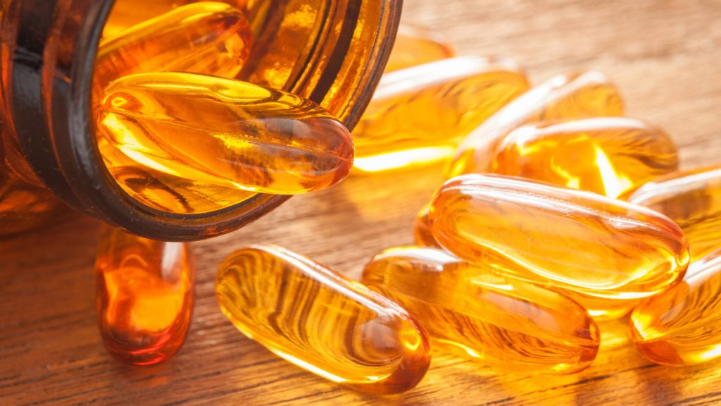 a close-up of an open bottle spilling fish oil capsules out onto a wooden surface