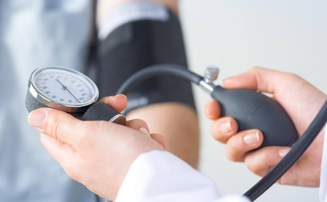 a person having their blood pressure checked by a medical person