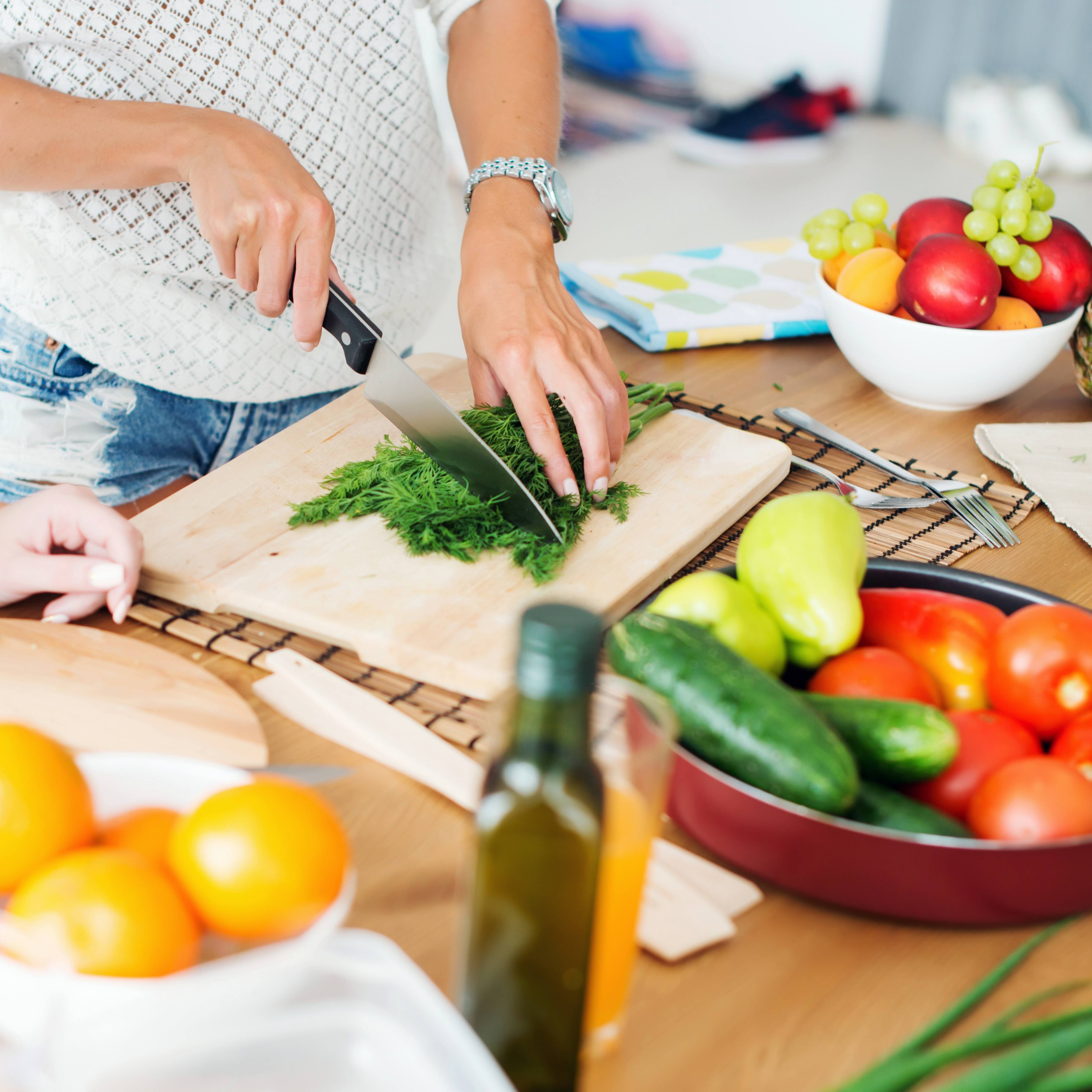 a woman slicing and cutting up fresh fruits and vegetables on a kitchen counter