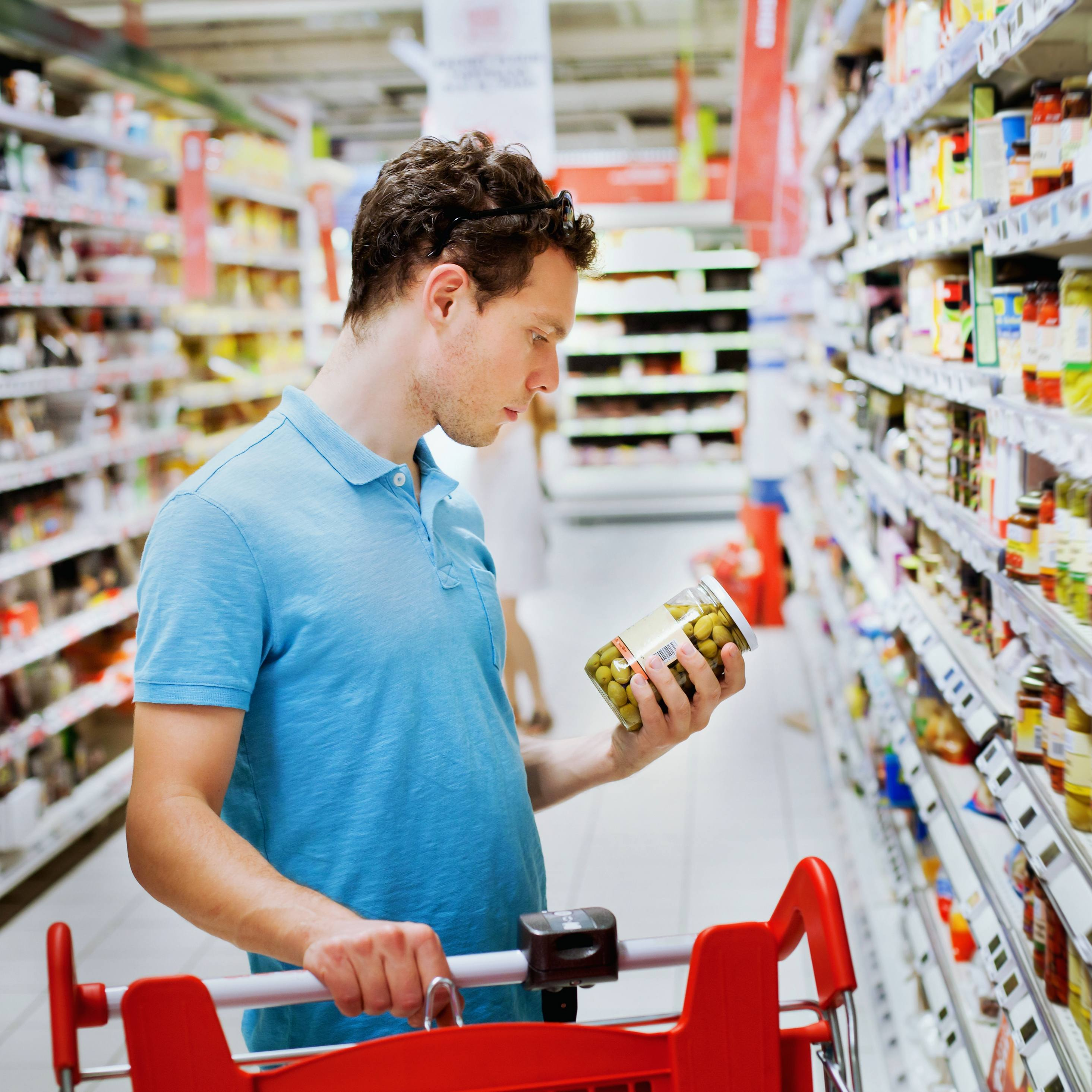 a young man shopping in a grocery store looking at the food labels