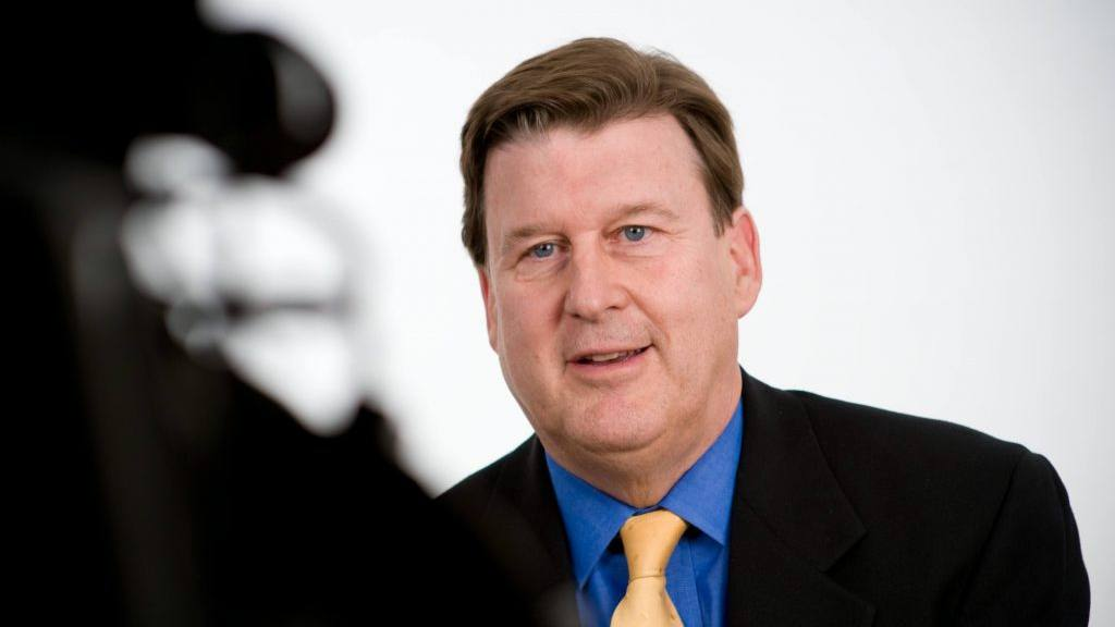 bio photo of Dr. Brott in a suit and tie during a video interview