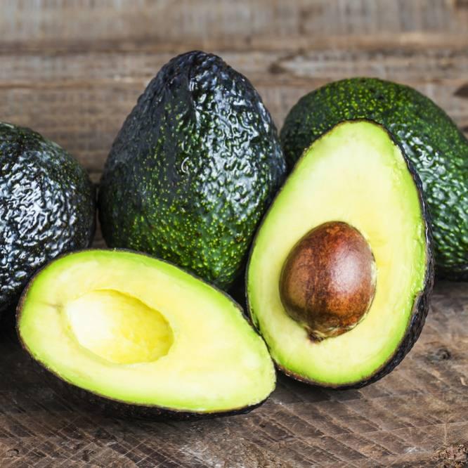 fresh avocados sliced on a wood cutting board