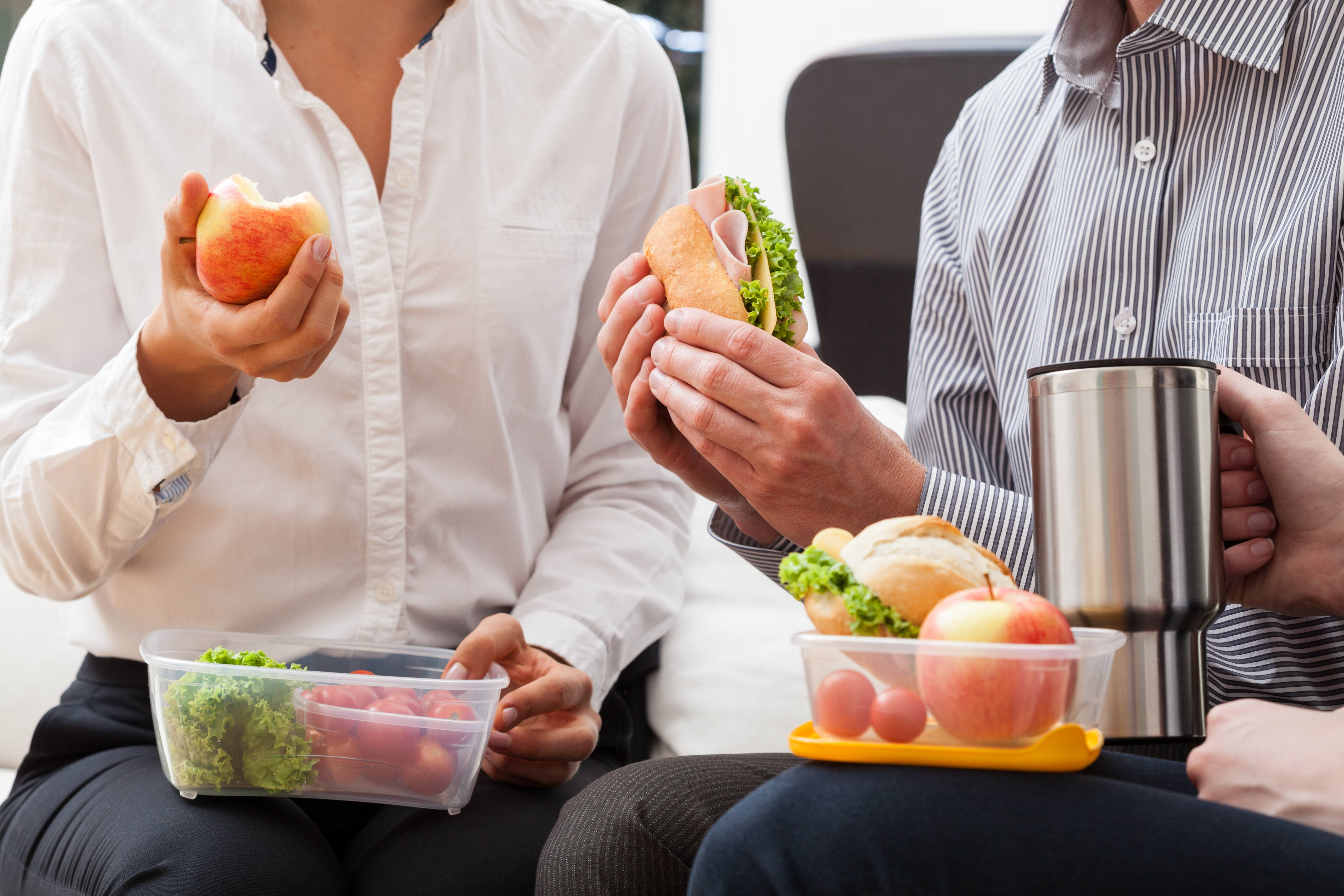 business people eating healthy lunch packed in home containers