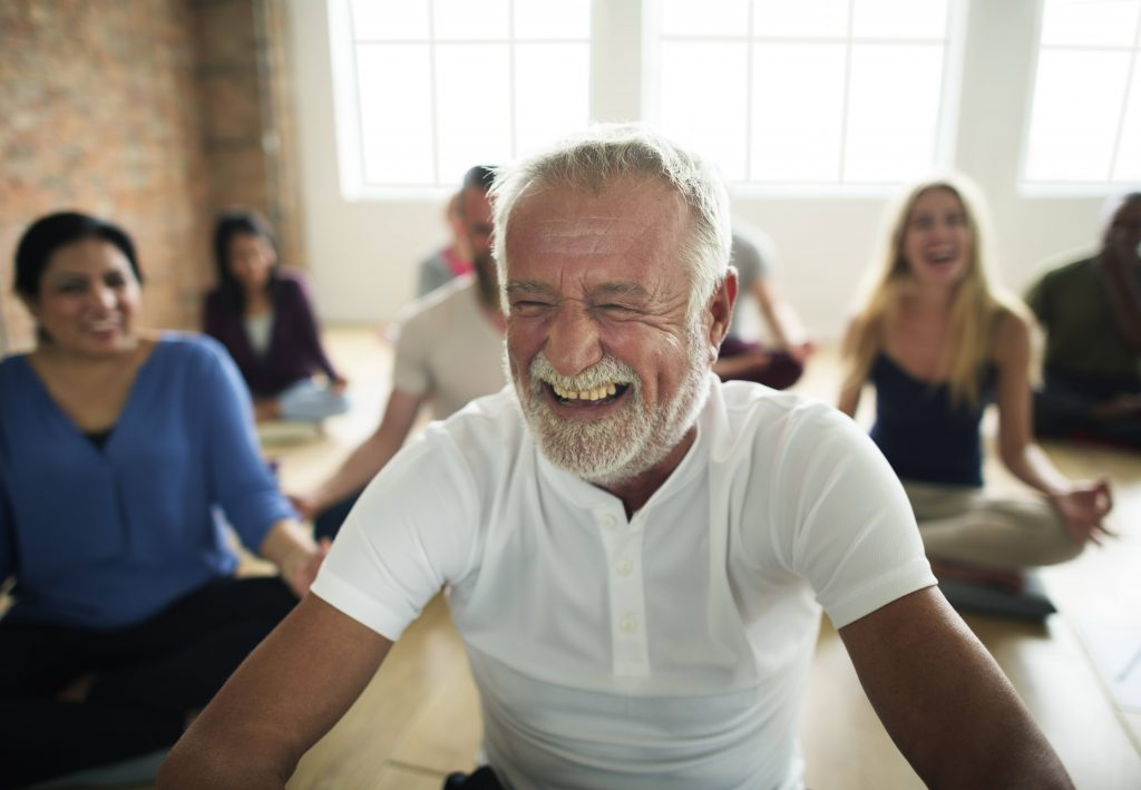 a group of smiling, laughing men and women in a yoga class