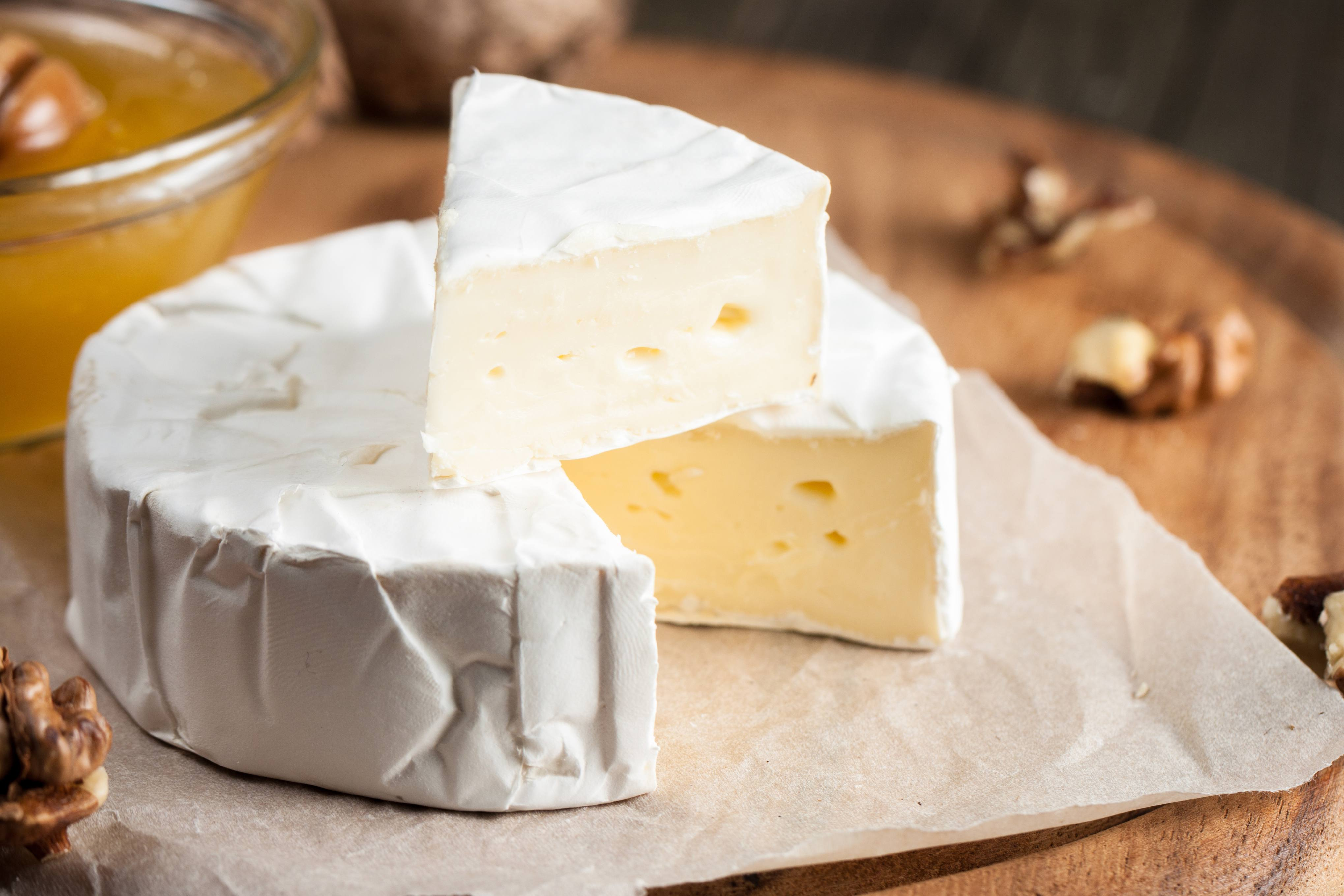 a fresh brie cheese wheel on a wooden cutting board