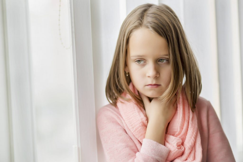 a little girl looking sad and sick, holding her sore throat