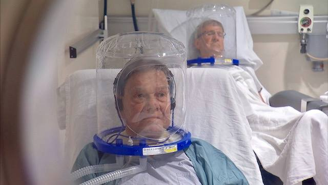 two patients in clear hyperbaric helmets on in the hyperbaric chamber
