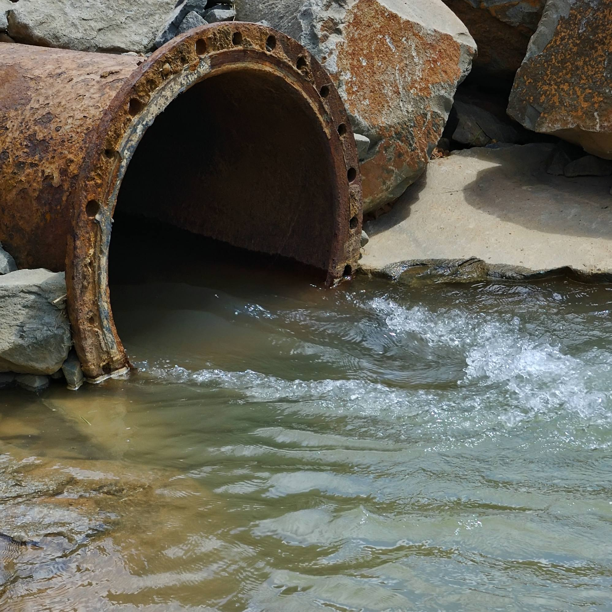 water pipe with rushing contaminated waste water from a street or factory