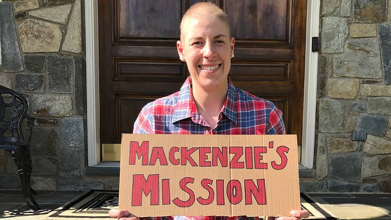 Mackenzie Boedicker who was diagnosed with amyloidosis, smiling and sitting outside on stairs holding a sign that says Mackenzie's Mission