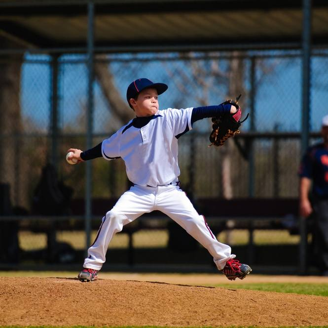 Youth baseball pitcher in wind up wearing white jersey