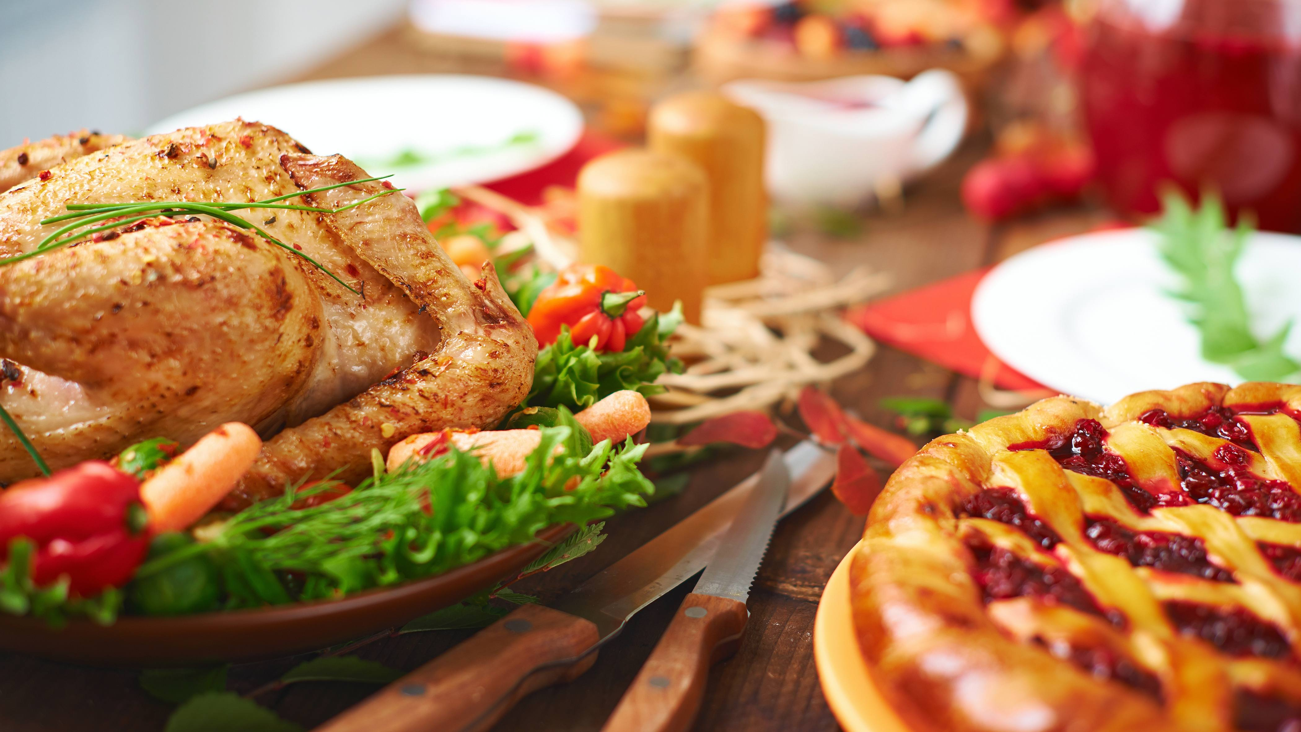 a festive holiday table with turkey, fresh vegetables and pie