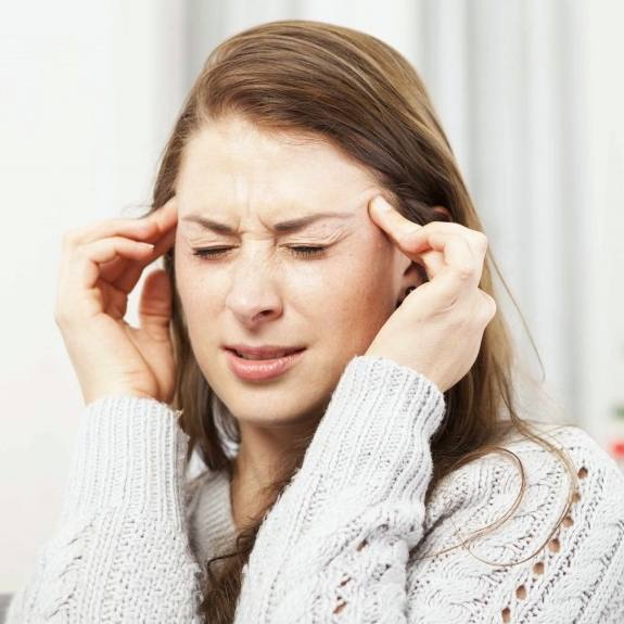 a woman holding her hands to her head as if she's tired or stressed, with a headache at the Christmas holidays