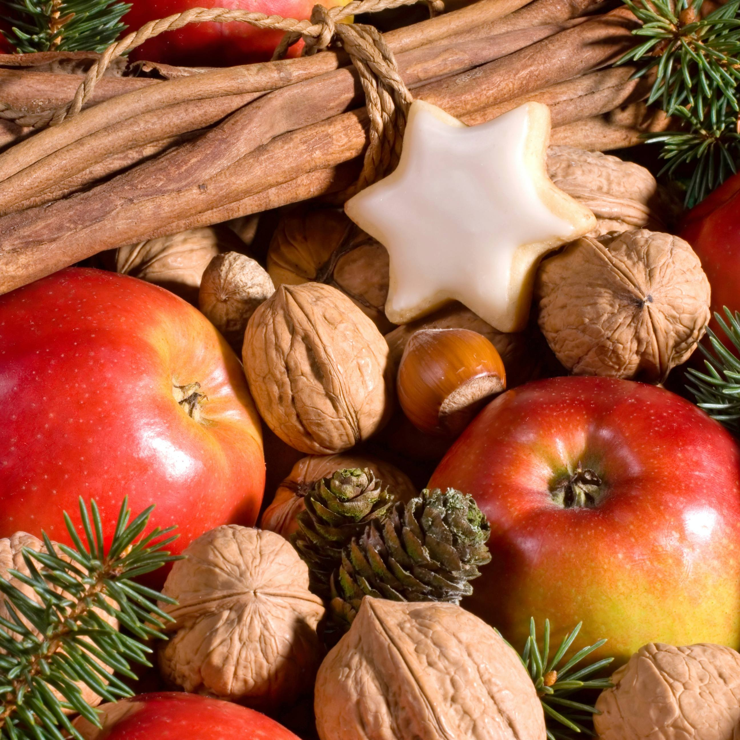 a festive arrangement of fresh apples, with walnuts and cinnamon sticks and evergreen branches