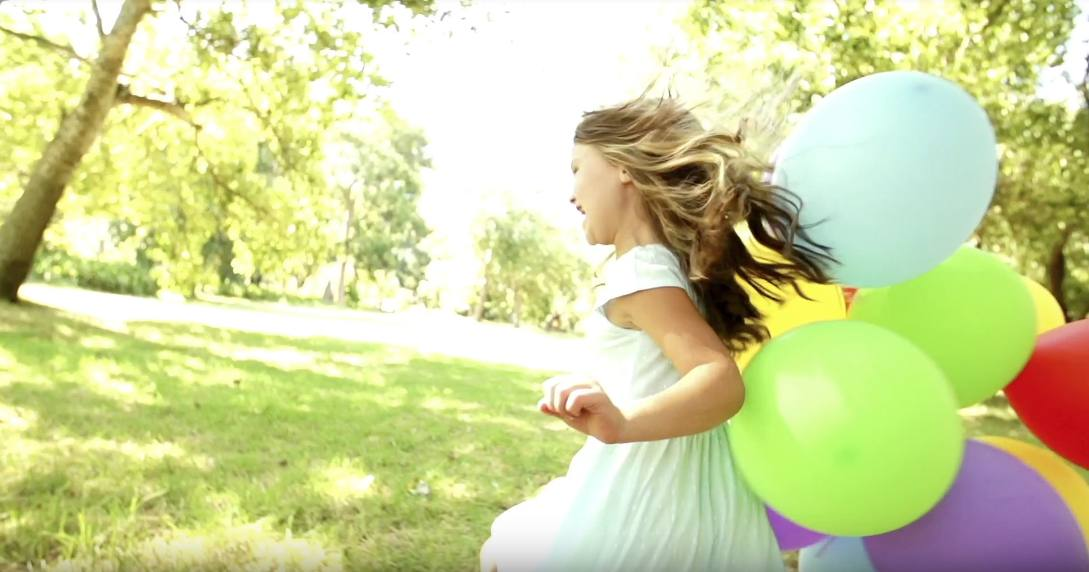 girl running with balloons outdoors