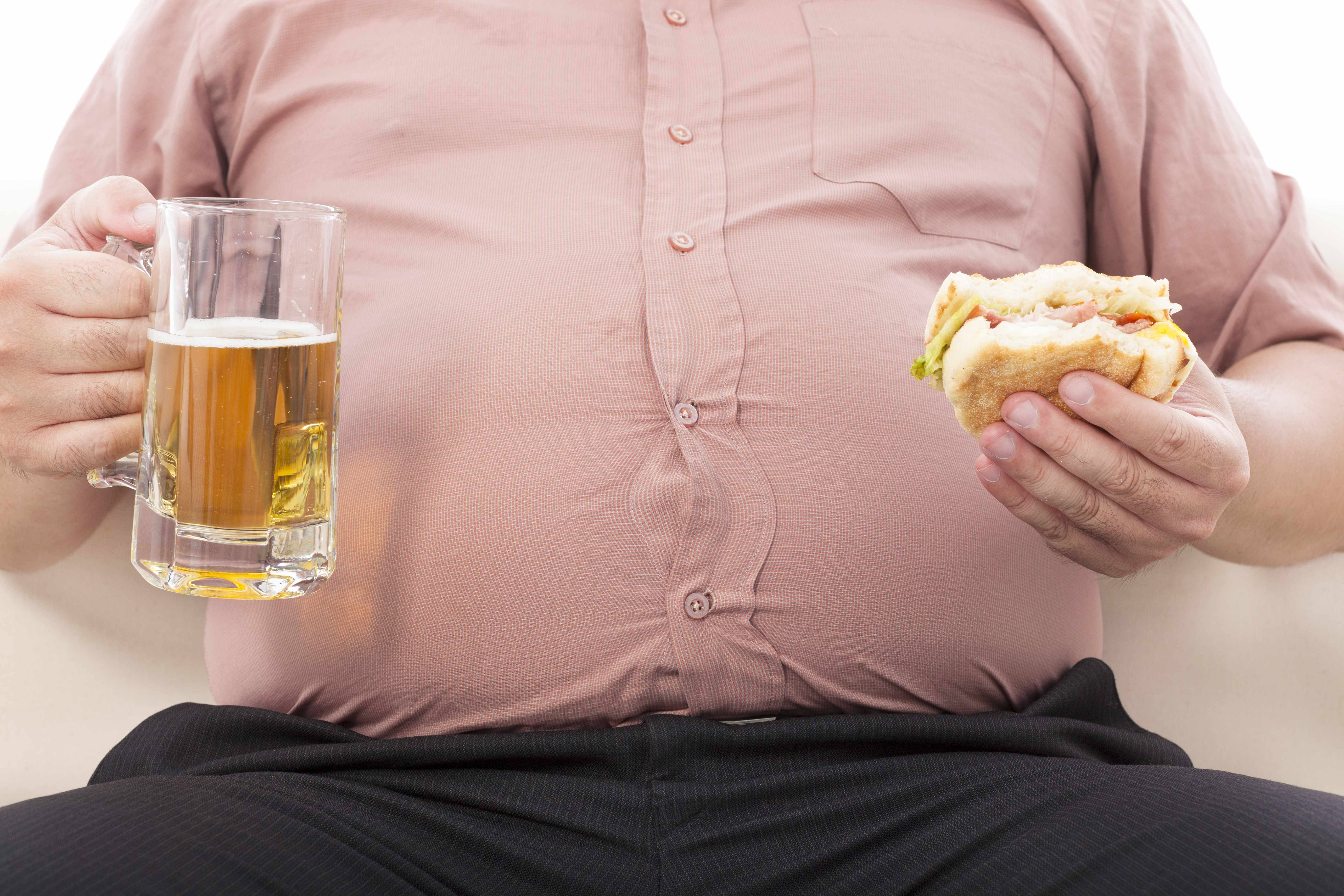 the mid-section of an overweight obese man holding a beer and a sandwich in front of his large belly