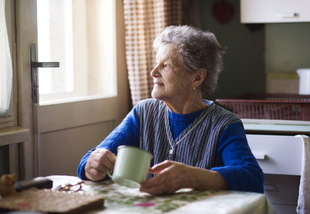 an elderly woman sitting at her kitchen table with a cup in hand, staring out the window