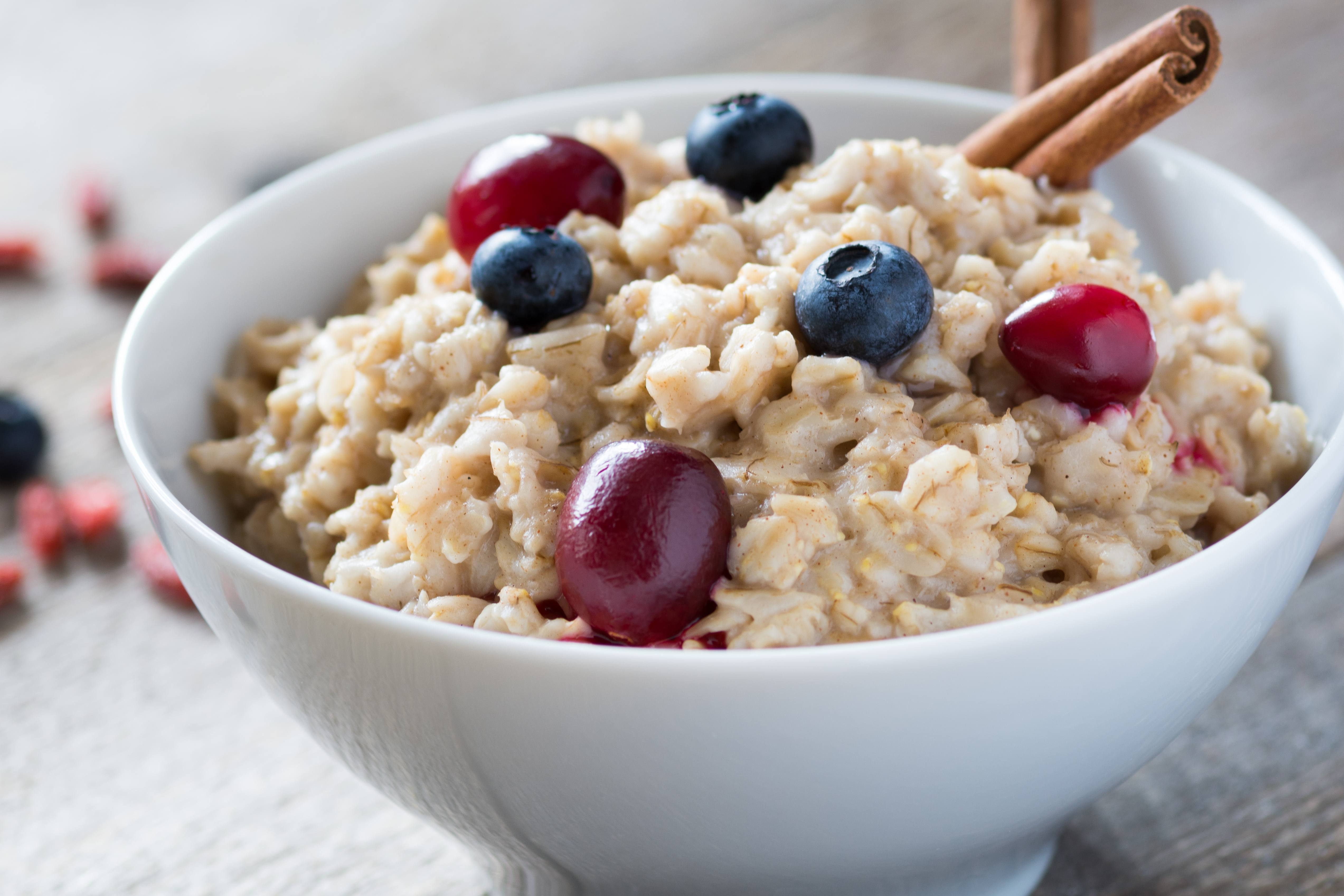 a white bowl of grain cereal topped with fresh fruit