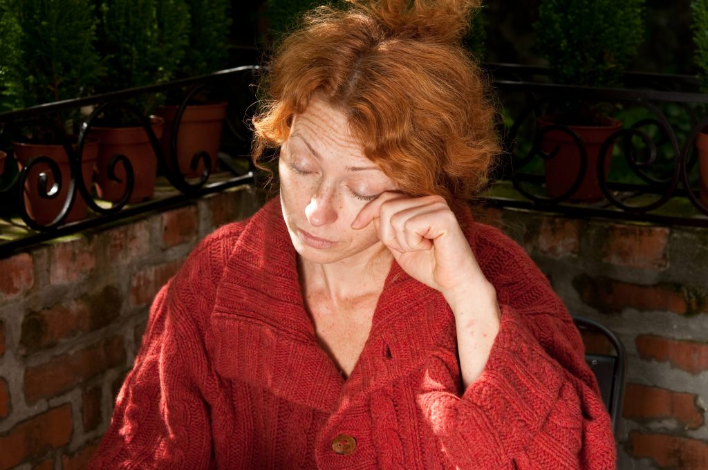 a middle-aged woman rubbing her eye, looking tired, depressed, sad