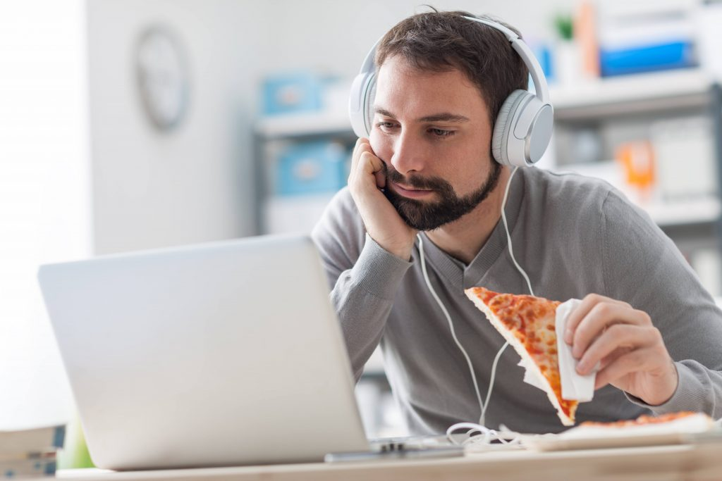 a young man alone in his work office, wearing headphones eating a slice of pizza and staring at his computer screen