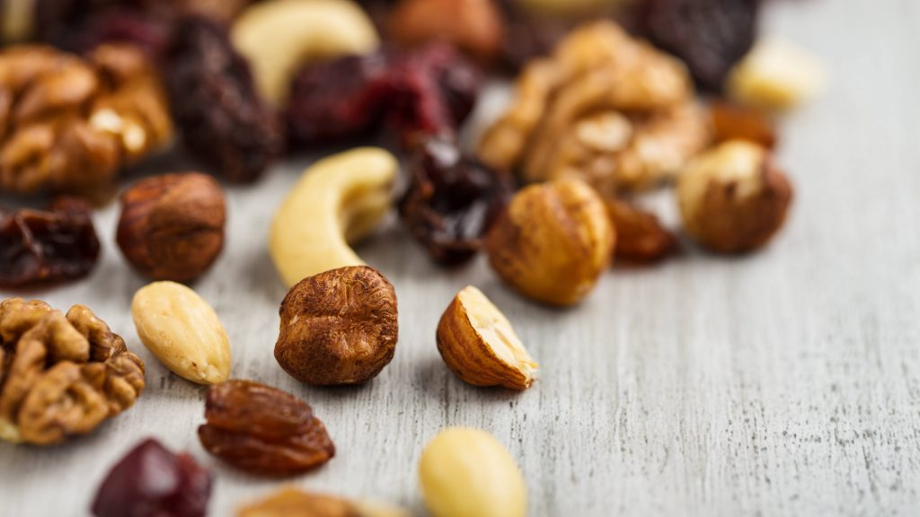 trail mix spilled out onto a wooden surface, including a variety of nuts and dried fruits