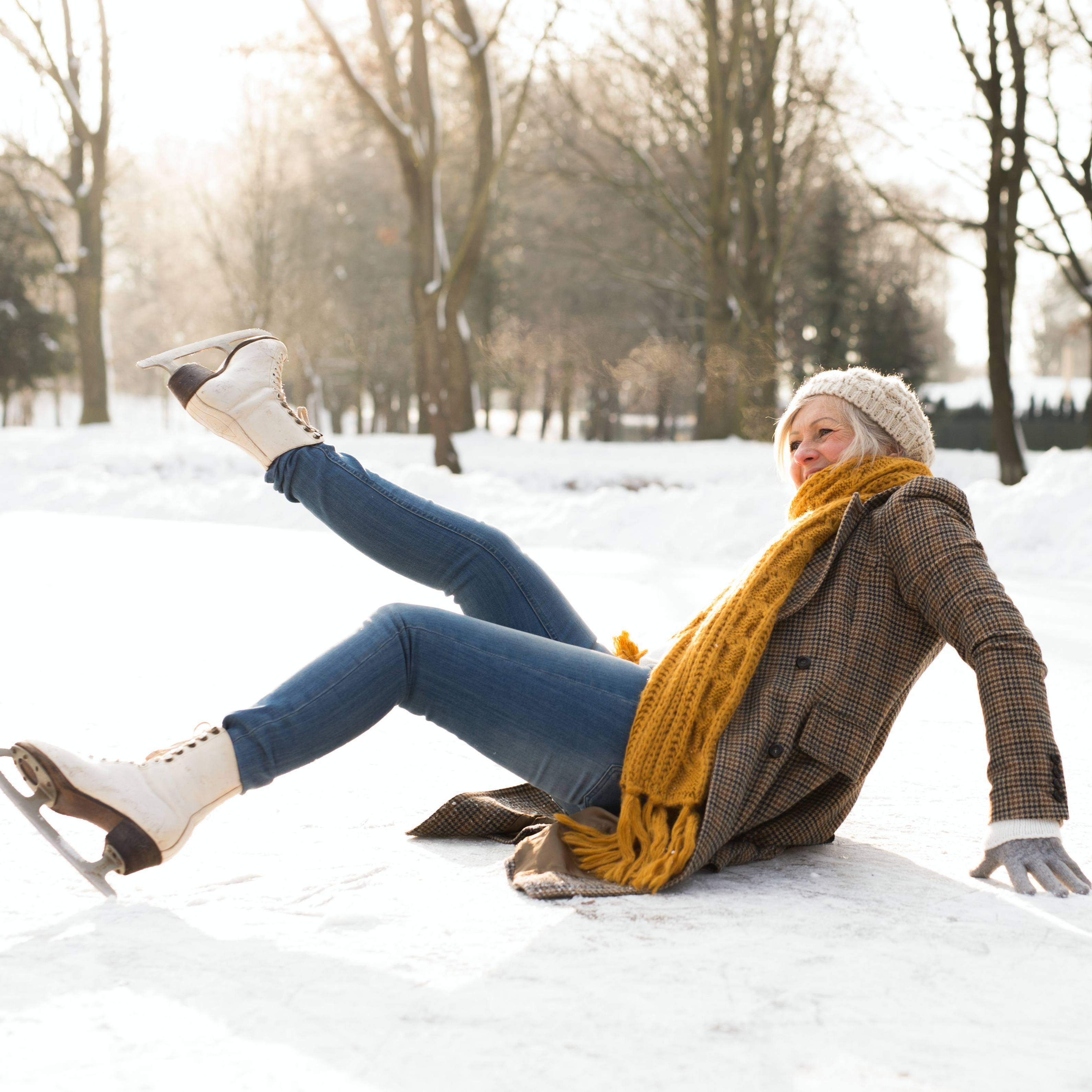 a woman with ice skates slipping andfalling on the ice in winter