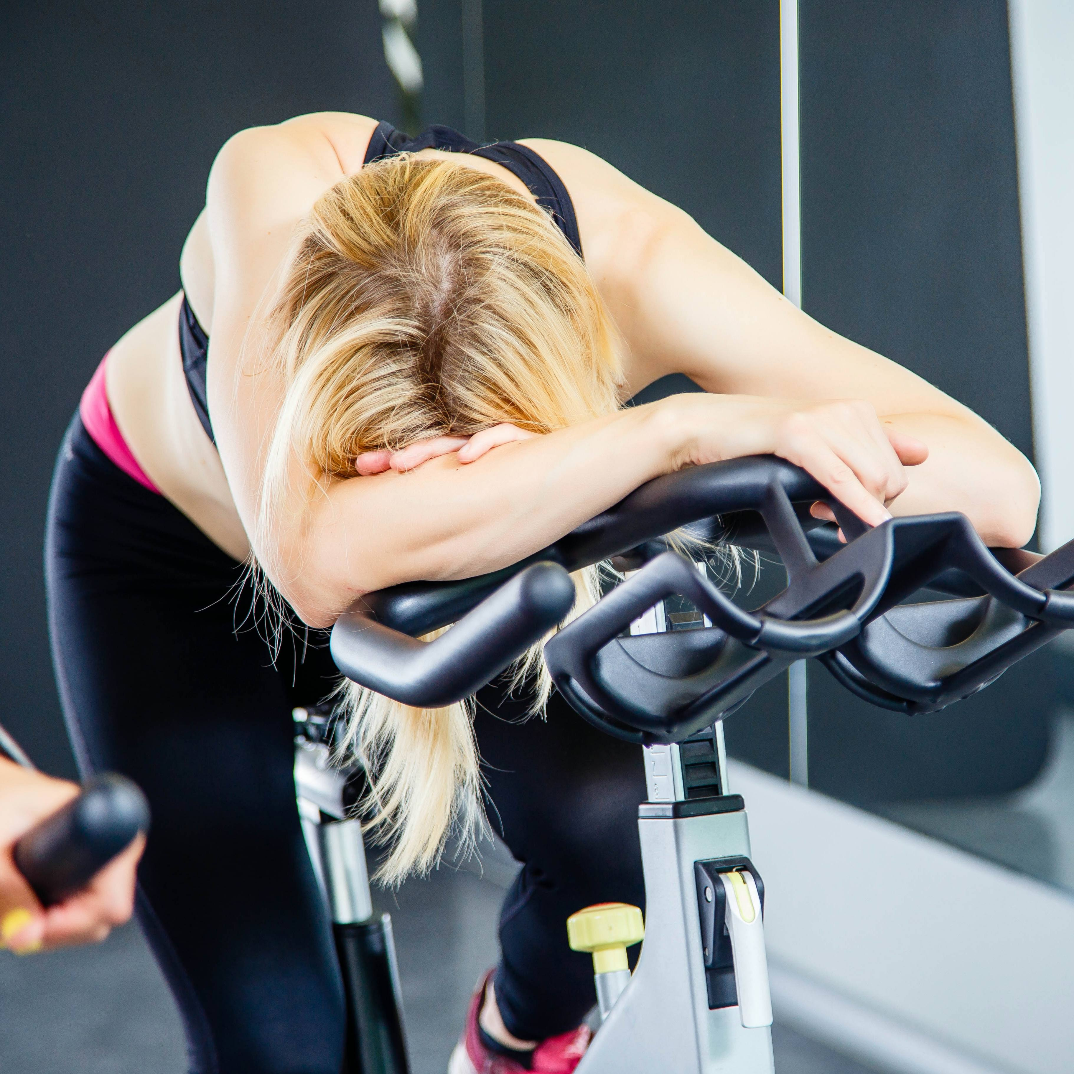 an exhausted woman exercising on a bike in a gym