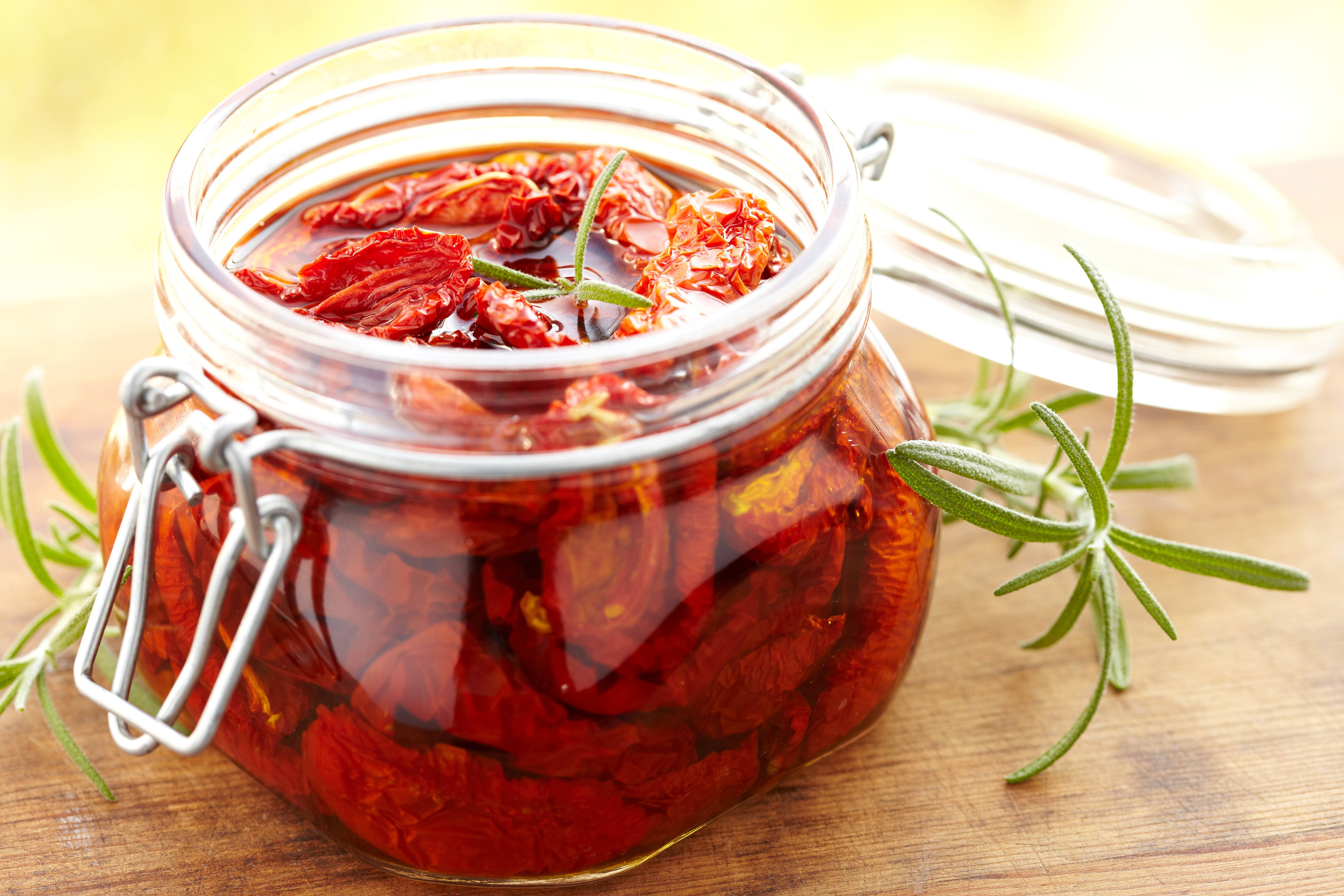 a jar of sundried tomatoes marinating for a vegetable pesto spread