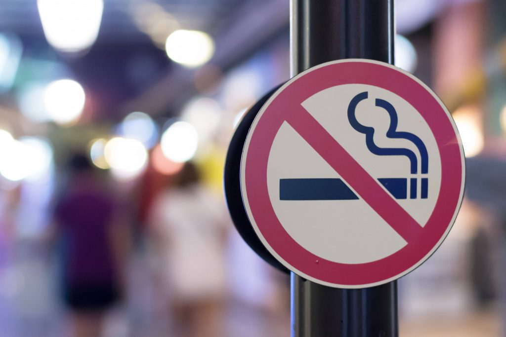 a close-up of a No Smoking symbol on a sign along a busy city sidewalk
