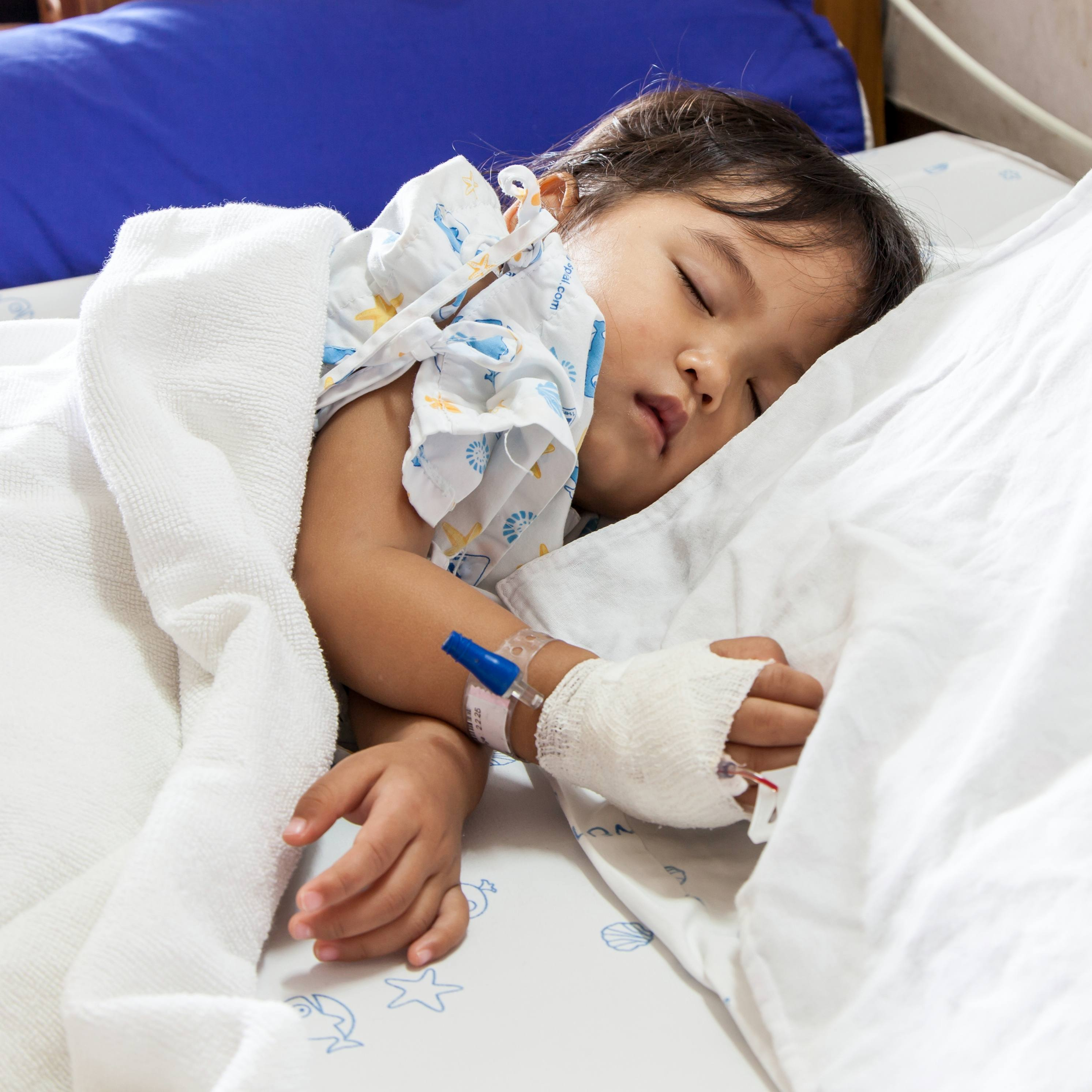 a sick child sleeping in a hospital bed with an IV in his or her hand
