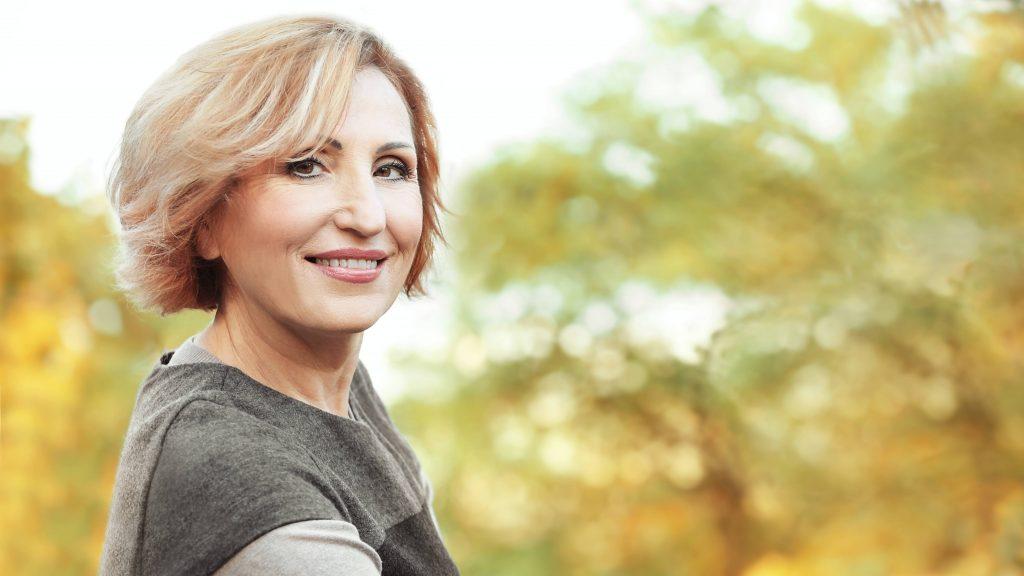 Una linda mujer de mediana edad en un parque otoñal