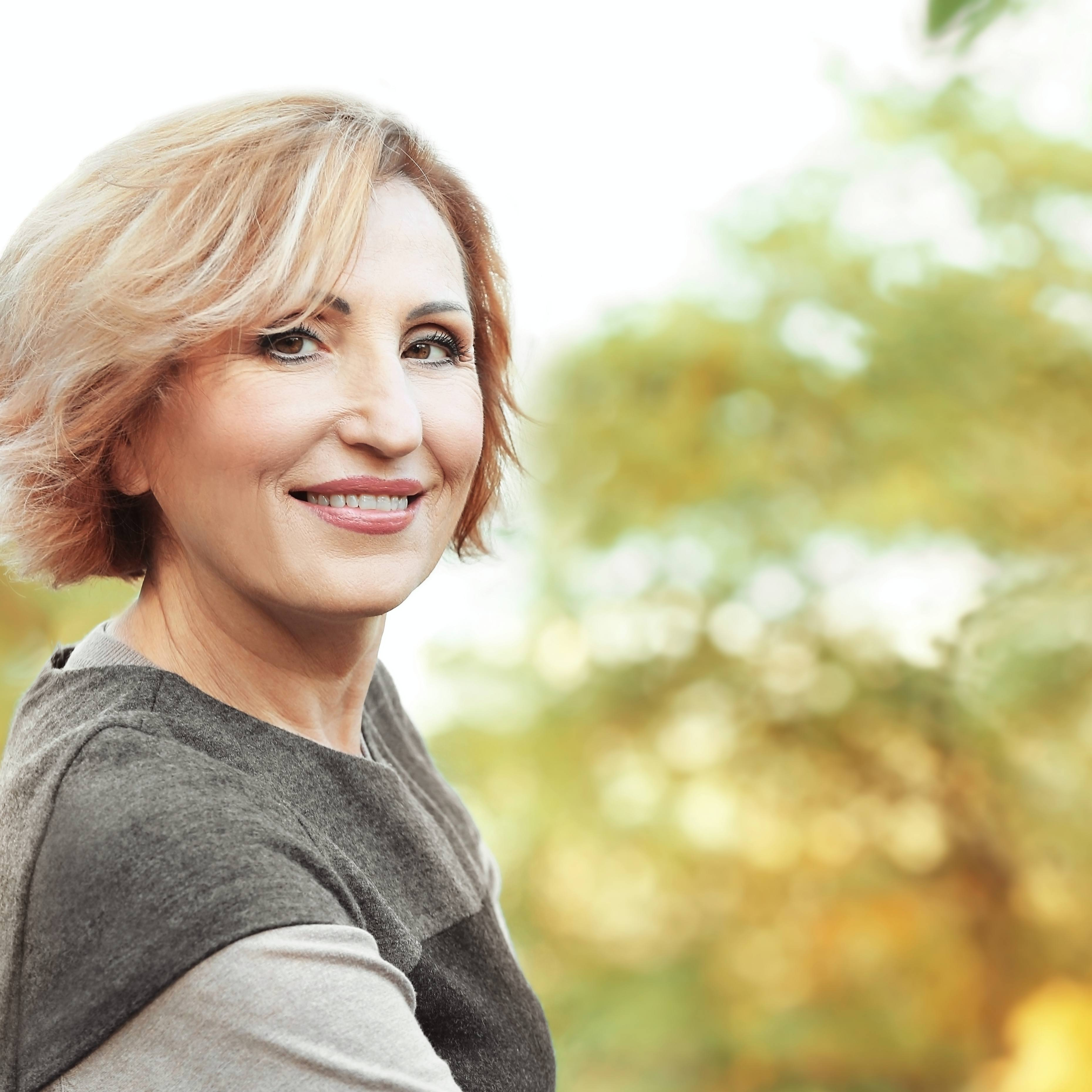 Beautiful middle-aged woman in autumn park