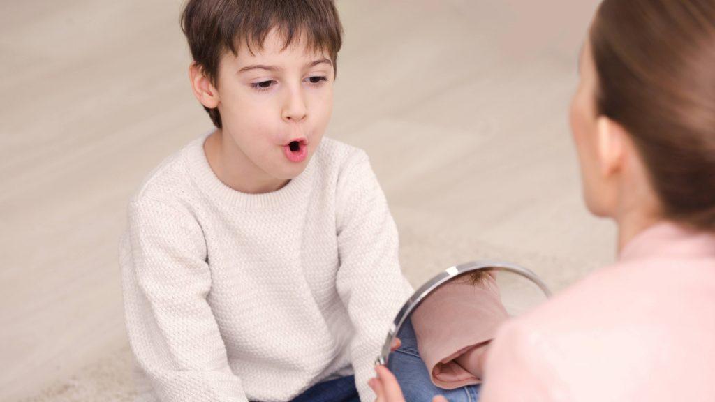 Un niño recibe terapia del lenguaje con una terapeuta que usa un espejo