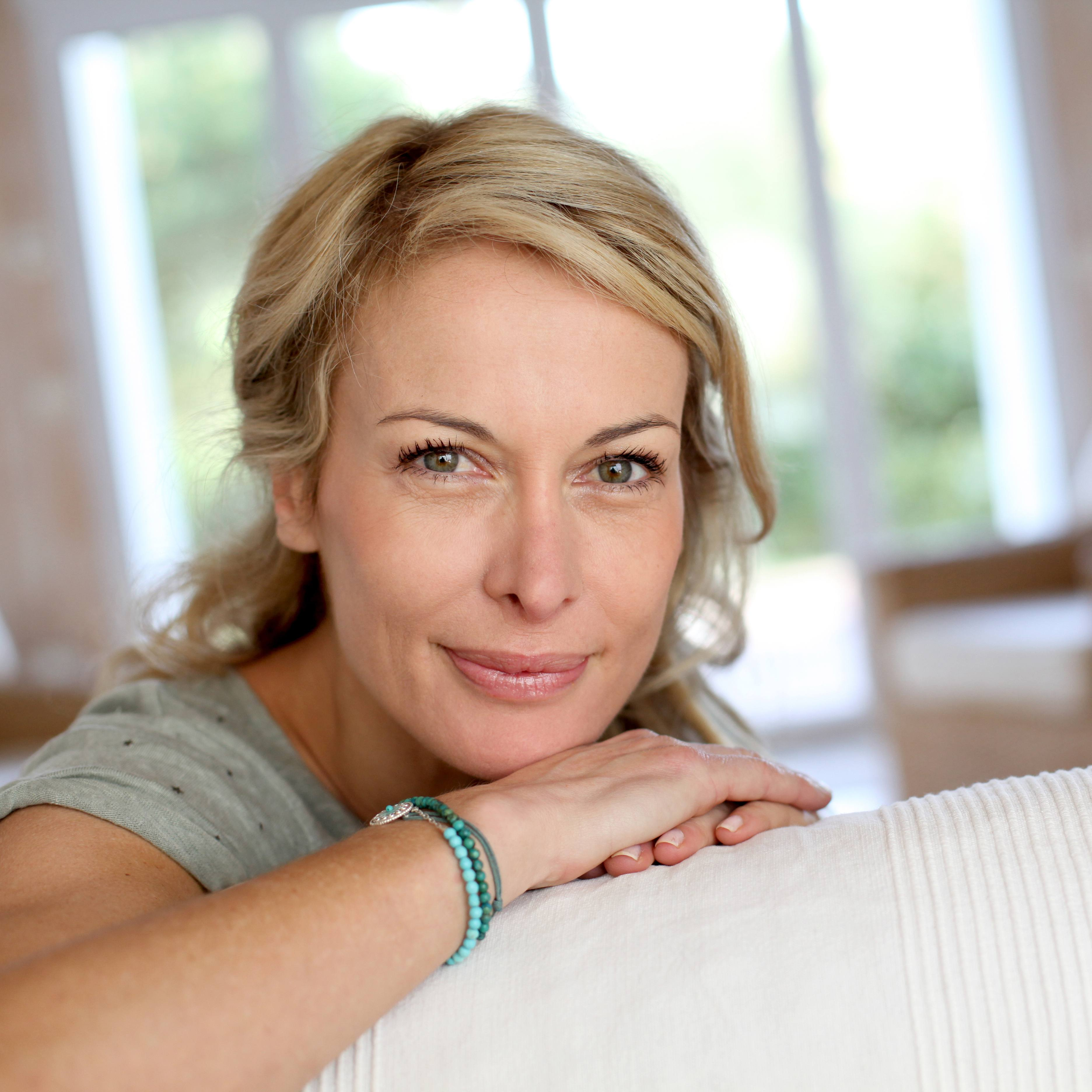 a close-up of a smiling middle-aged woman looking over the back of a couch