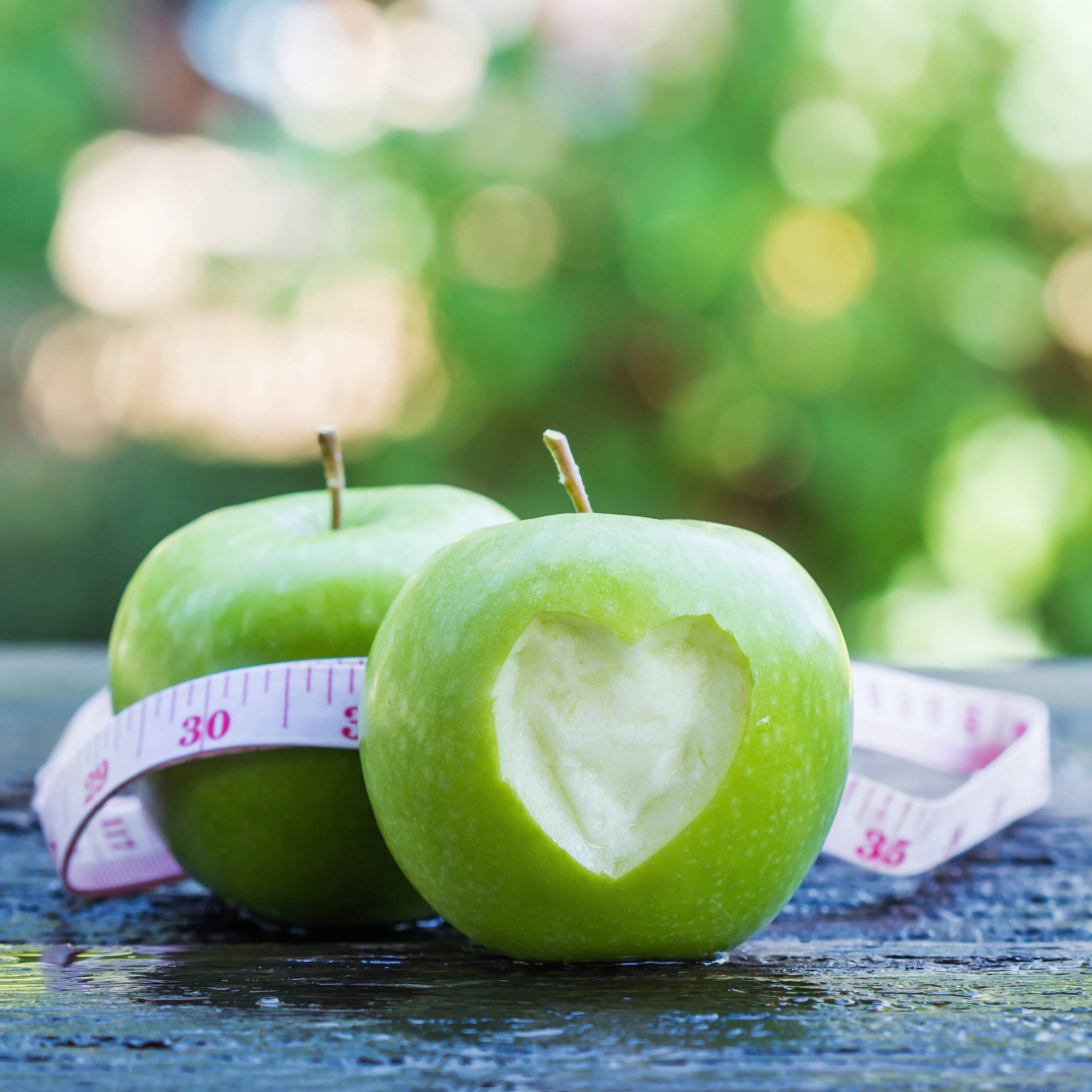 green apples with a heart carved in the skin and a tape measure around the apple representing weightloss and healthy eating