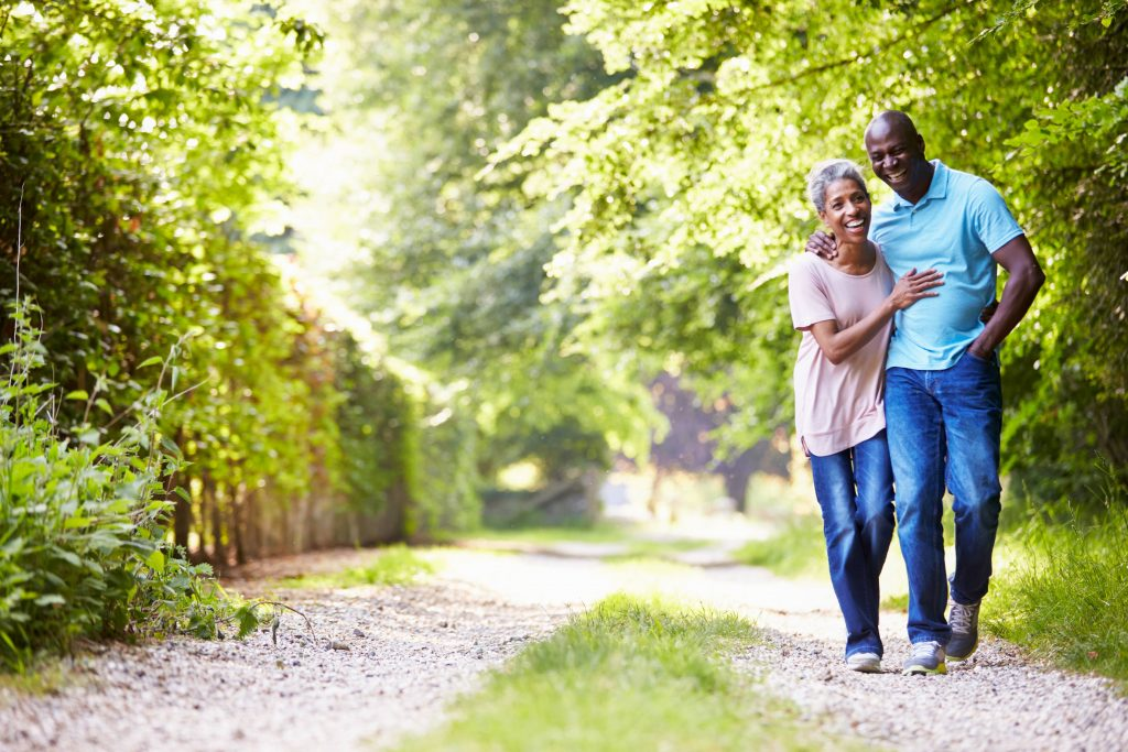 a happy, smiling middle-aged couple walking with their arms around one another down a dirt path, surrounded by trees and sunshine