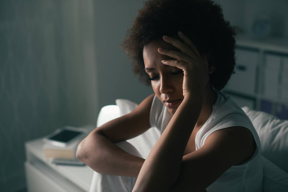 a young woman in a dark bedroom, sitting up in bed with her eyes closed and her hand to her forehead, suffering from insomnia or depression or stress