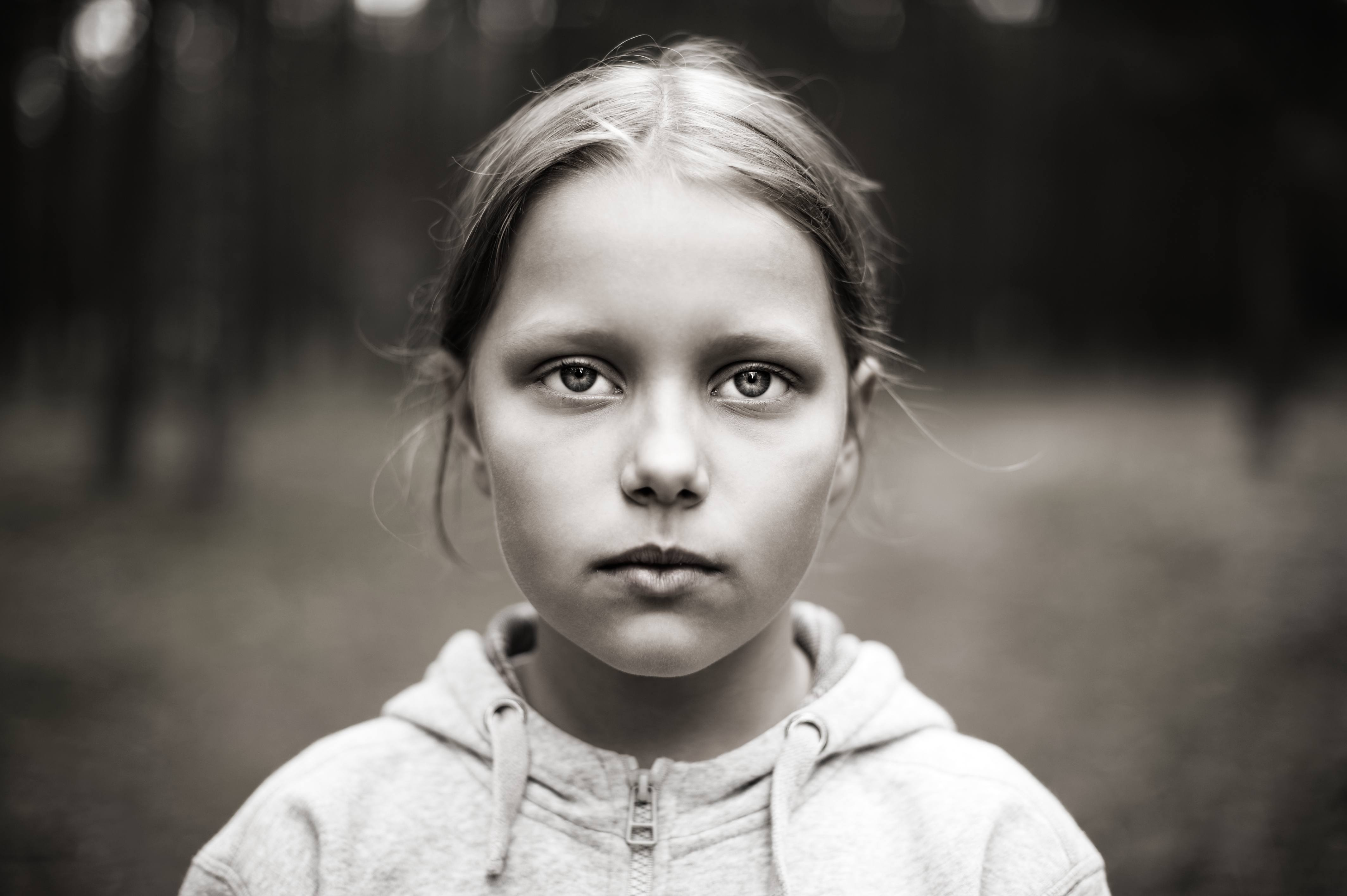 a young serious, frightened and sad looking girl in a black and white photo