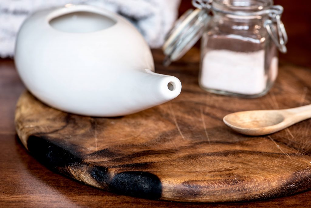 a neti pot, canister of salt and small wooden spoon