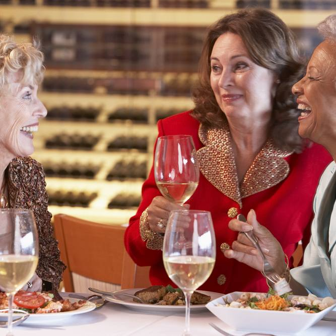 three older women, talking and laughing over dinner and wine