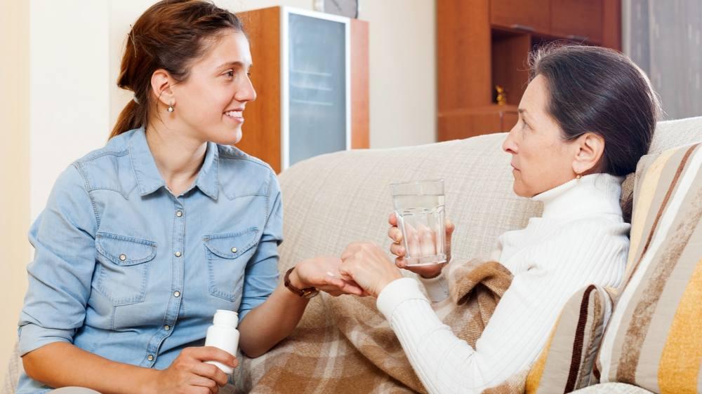 Una mujer le da el medicamento a su madre en la casa
