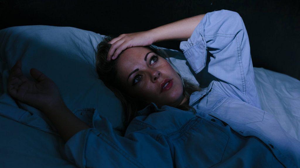 Una mujer joven está acostada en una habitación oscura, con los ojos abiertos y las manos sobre la frente porque sufre de insomnio y estrés.