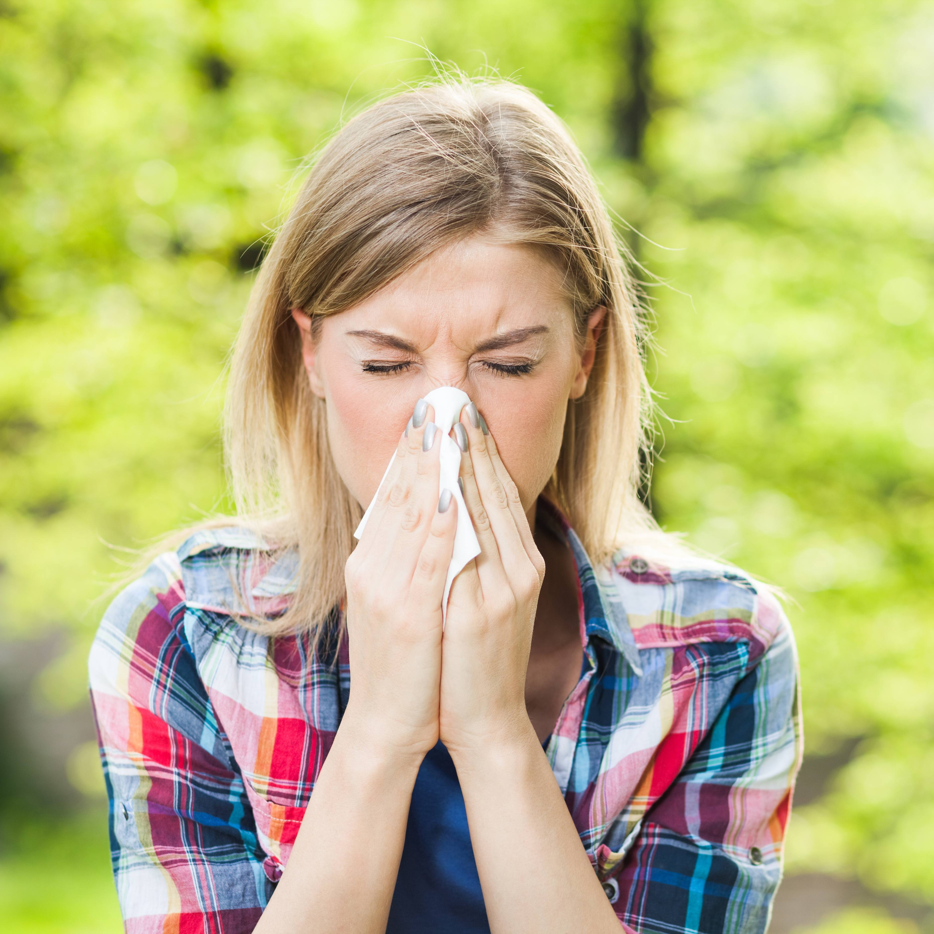 a young woman outside on a bright spring day, sneezing or blowing her nose into a tissue
