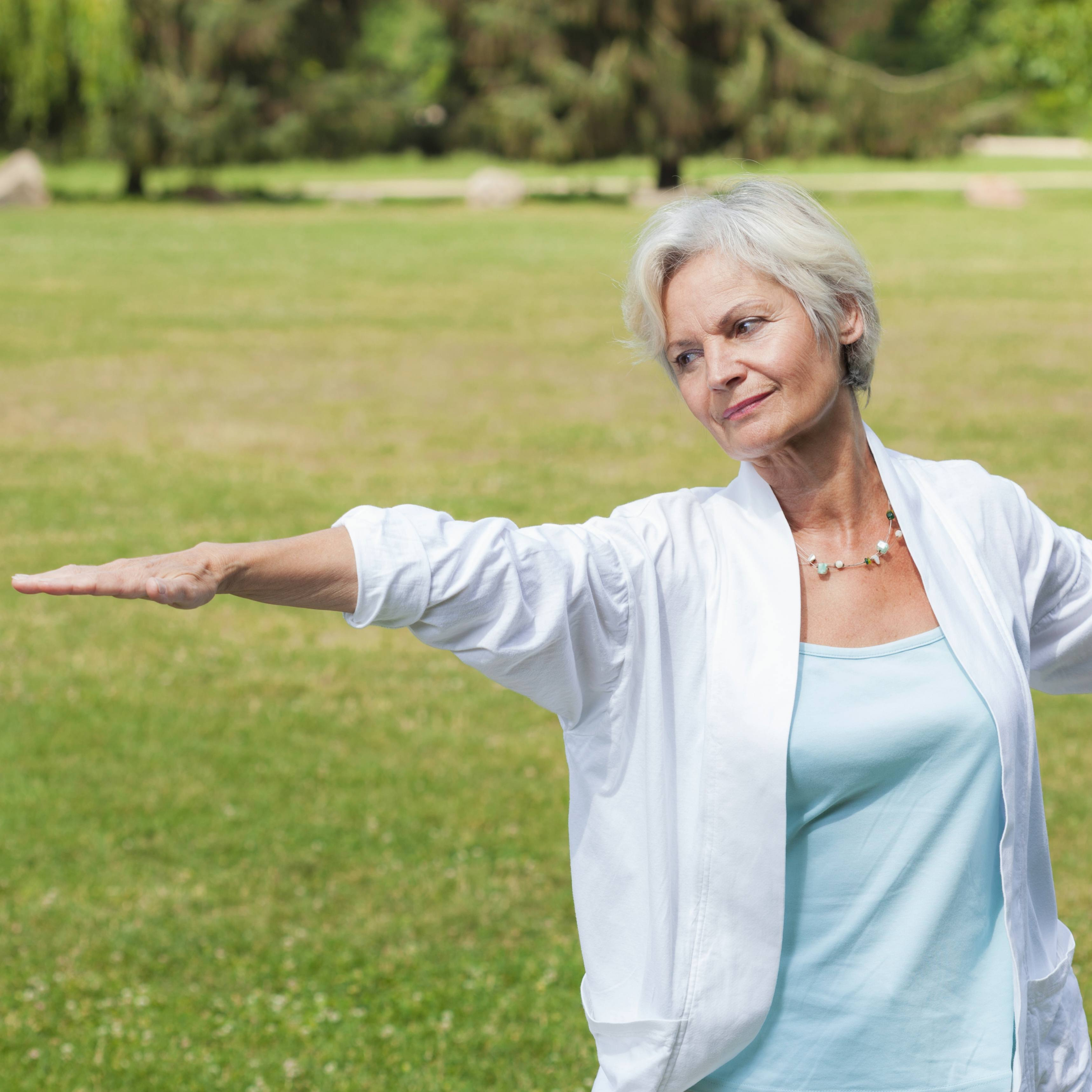 an older women outside on green grass exercising and practicing the art of tai chi for balancing