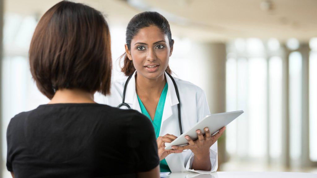 Una doctora conversa con su paciente en el consultorio