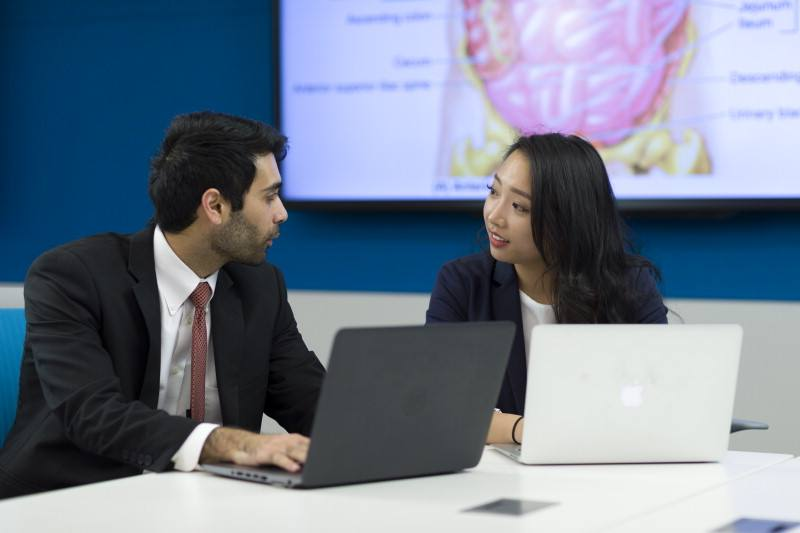 two Mayo Clinic Arizona residents sitting at a, working on their laptops, and in discussion