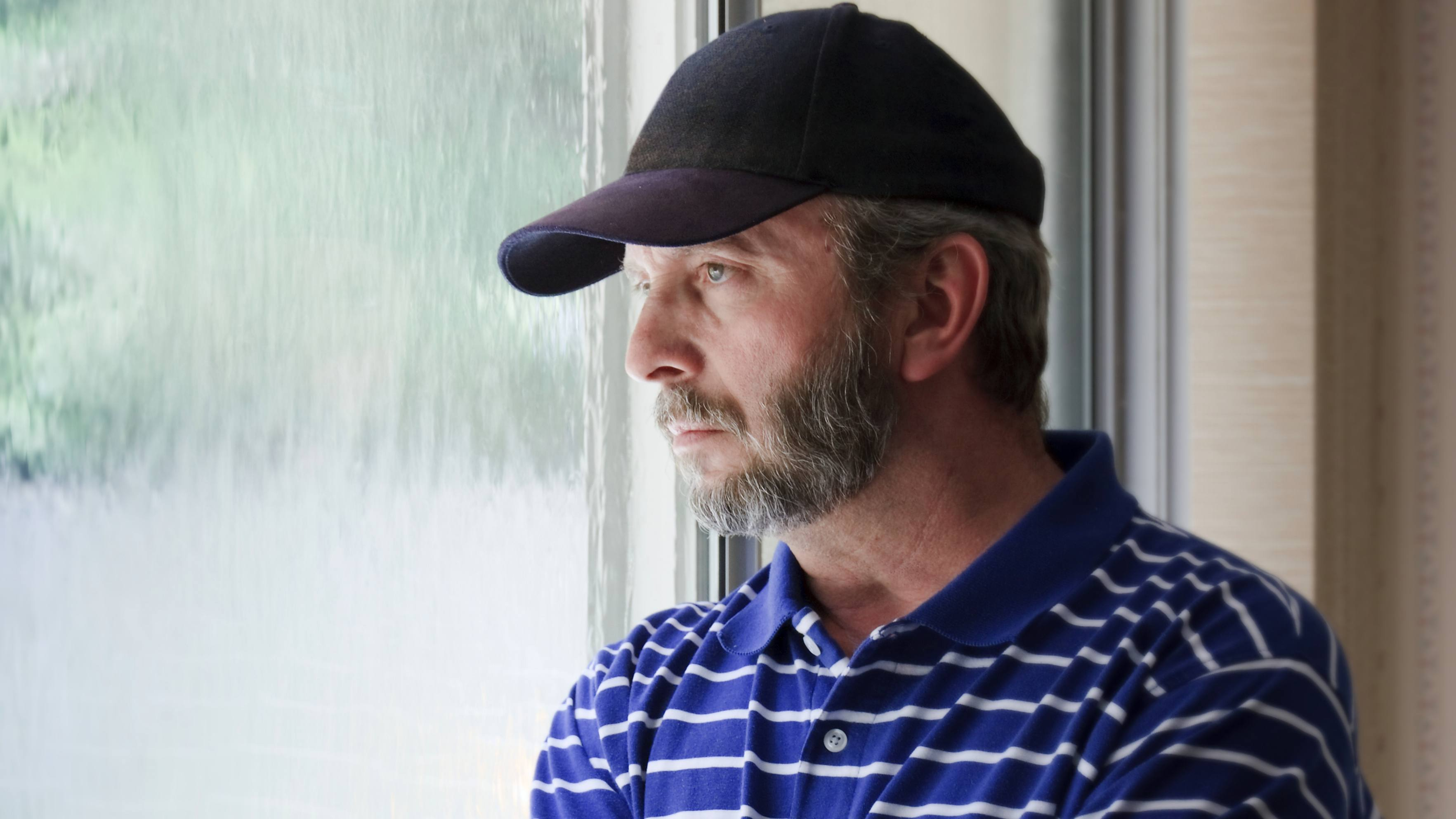a middle-aged man wearing a baseball cap and staring out a window looking sad, thoughtful, depressed, worried