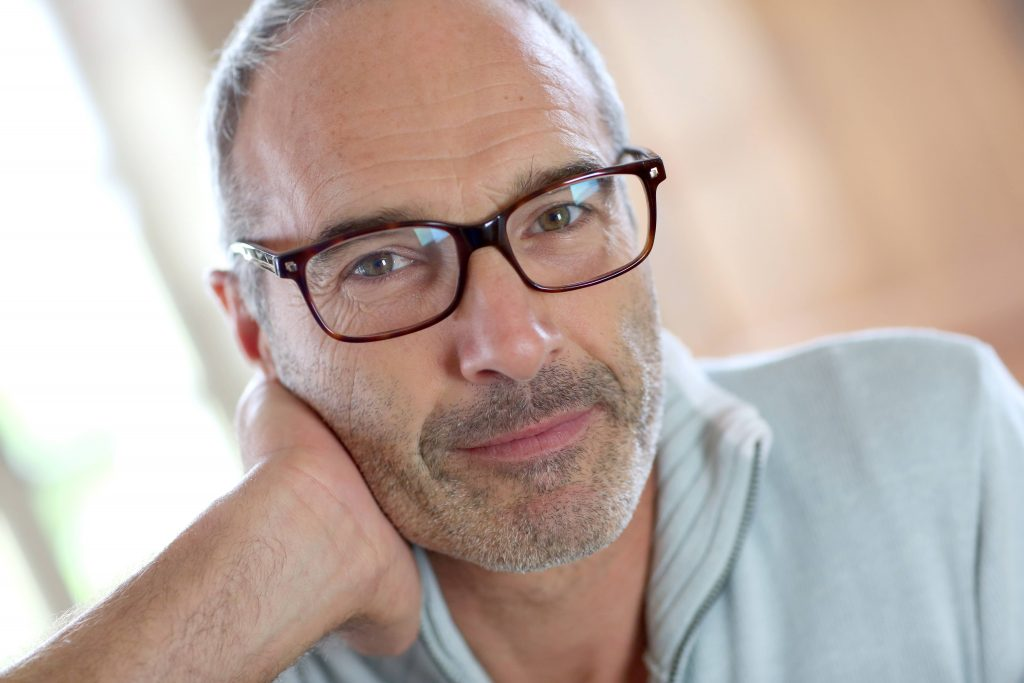 a close-up of a smiling middle-aged man, wearing glasses, resting his cheek on his hand