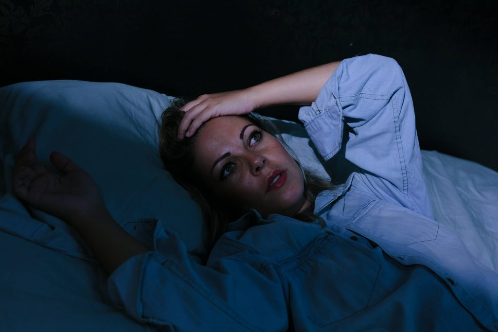 a young woman in a dark bedroom, lying in bed with her eyes open and her hand to her forehead, suffering from insomnia or stress