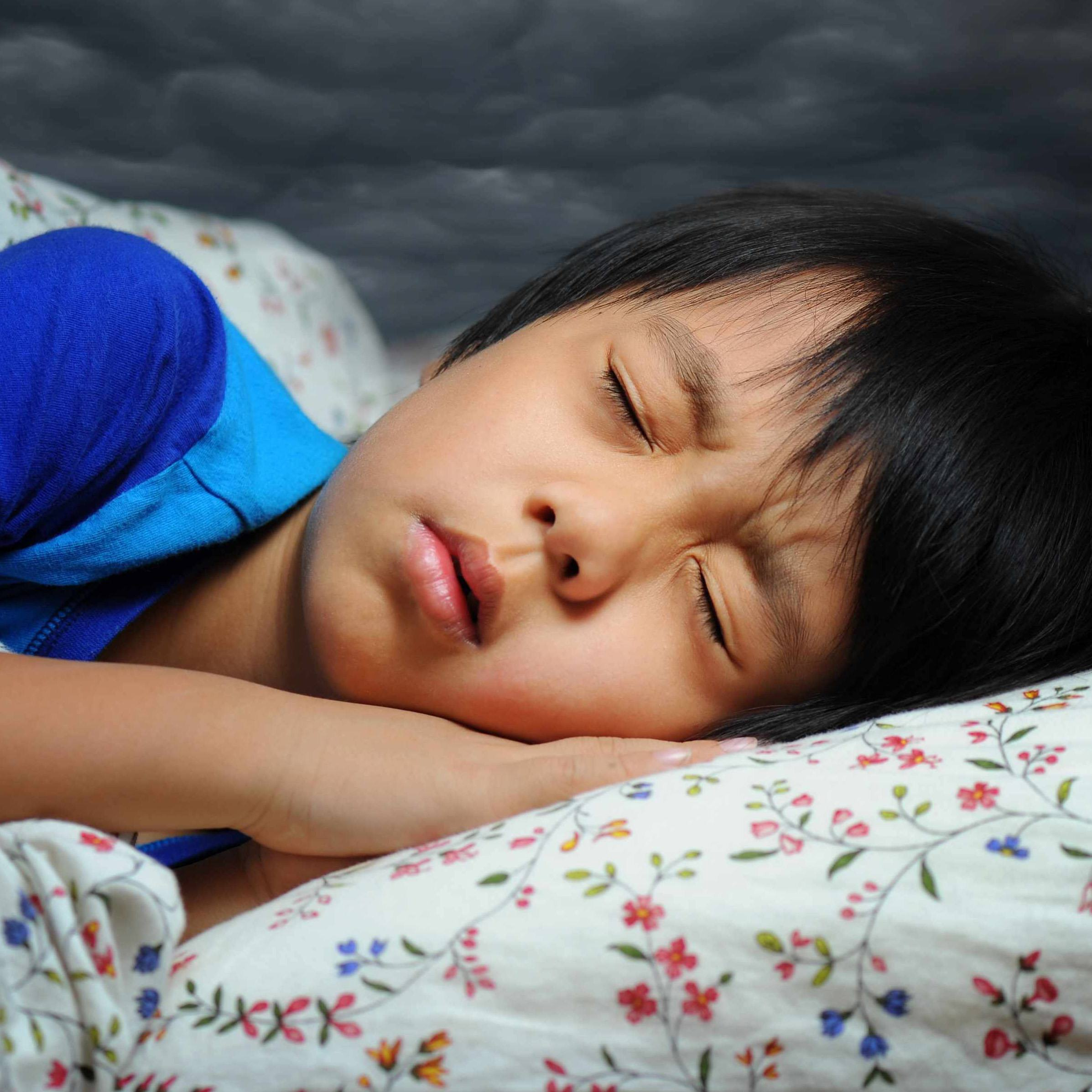young child is sleeping bed and having a possible nightmare dream